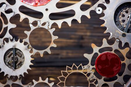 GIANT OLD AND RUSTY COGWHEELS WITH WOODEN BACKGROUND