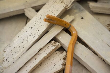 Crowbar on demolished wood eaten by woodworms