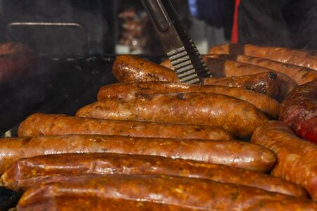 Grilling different kinds of sausages, dry and fresh meat on open barbeque