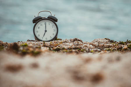 ALARM CLOCK AT THE BEACH WITH TRENDING COLORS. CONCEPT OF SUMMER ENDING AND WELCOMING AUTUMN
