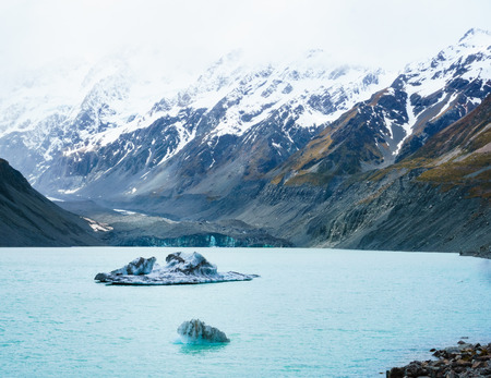 Two irregular icebergs floating in Hooker Lake, New Zealand. Glacier in the background shadowed over by rugged snow capped mountains. Stock Photo
