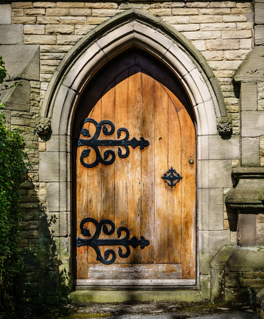 Arched stone entrance to medieval style building. Worn wooden door with ornate back hinges. Gives sense of mystery and exploration.