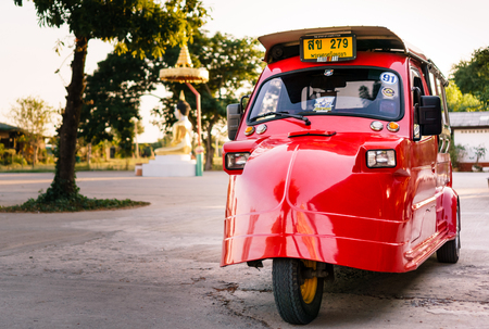 Bright red immaculate tuk tuk in foreground. In the background is a defocused white and gold buddha statue. Image can be used for travel, adventure, Thailand themes.