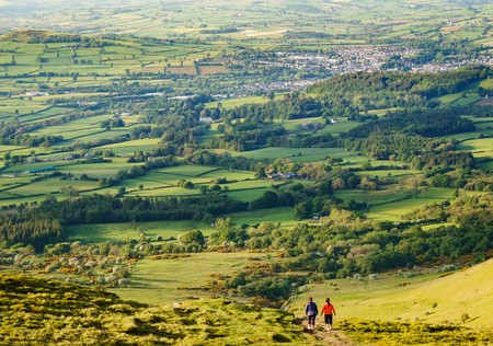 brecon beacons: Two women walking away off of hill top in sports gear. Farmland and town in the distance. Taken in Wales during golden hour. Stock Photo