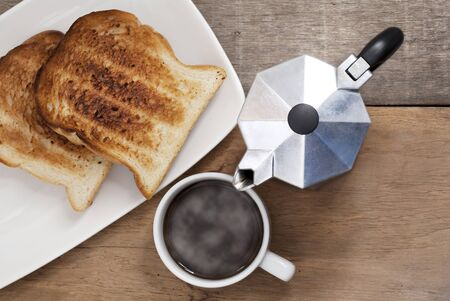 Coffee cup and toast on the wooden table