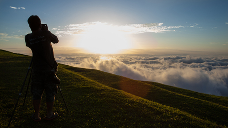 Photographers takes pictures fog from the top of mountain