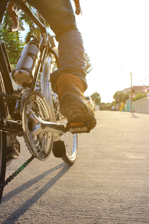close up: Detail of cyclist men feet riding road bike on the village