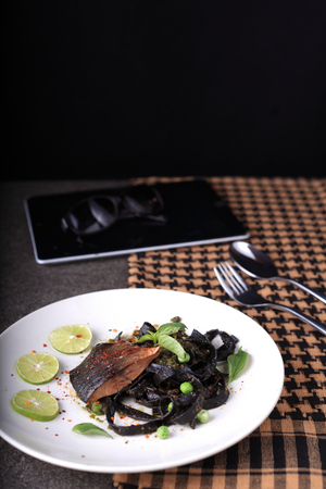 squid ink fettuccine pesto sauce with rainbow trout steak on white plate