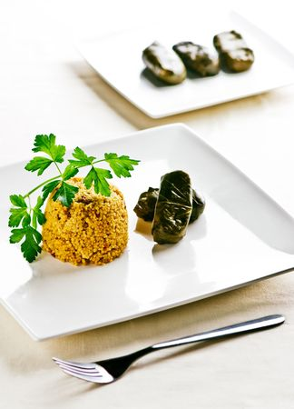 A main plate with couscous and vine wrapped rice. In the background is a second plate more food.