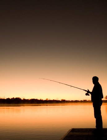 The silhoutte of a man fishing in the river at sunrise. Stock Photo