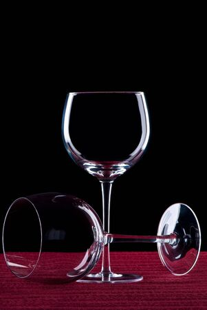 A pair of wine glasses on red cloth and a black background.