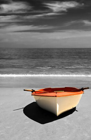 A row boat on the beach with selective colouring.