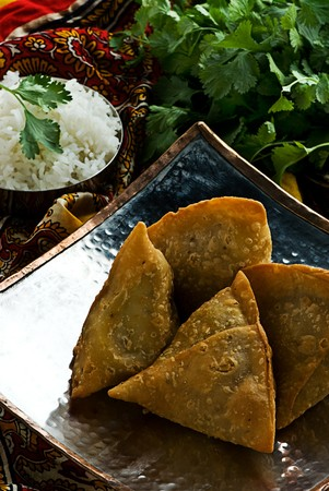 Indian samosas on an ndian style metal plate with rice. Garnished with fresh cilantro.