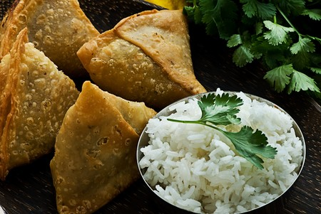 Indian samosas on a wooden plate with rice. Garnished with fresh cilantro.