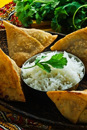 finger food: Indian samosas on a wooden plate with rice. Garnished with fresh cilantro.