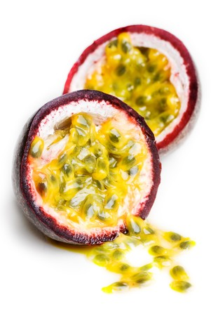 A passionfruit split in half with the seeds falling out. Stock Photo