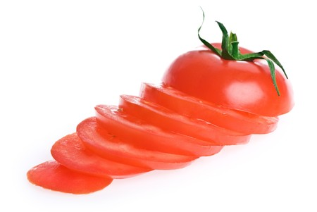 A whole sliced tomato, isolated on white.
