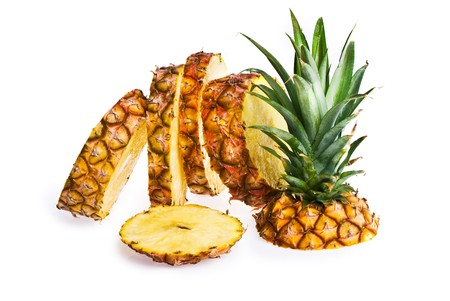 A pineapple sliced up, isolated on white. Stock Photo