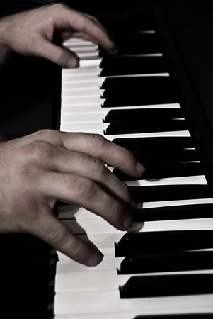 Close up of two hands playing the piano.