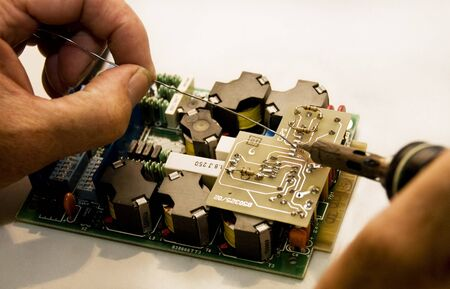 A man using a soldering iron on a circuit board. Stock Photo