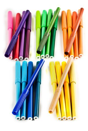 5 piles of 5 markers. Each pile is seperated by colour. Blue, Green, Orange, Purple and Yellow. Isolated on white. Stock Photo