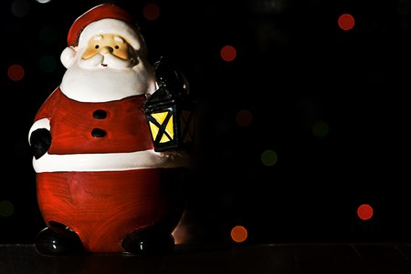 A christmas ornament of Santa holding a lantern. Lights on a christmas tree are in the background. Stock Photo