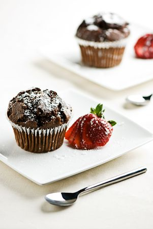 2 plates withchocolate muffins garnished with a strawberry.