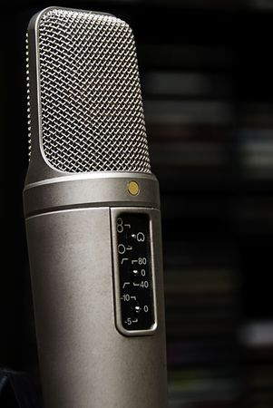 A studio Mic with out of focus CD rack in the background.