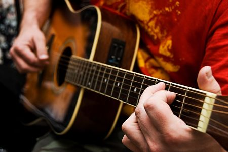 acoustic: A close up of a guitarists hands playing acoustic guitar. Narrow depth of field. Stock Photo