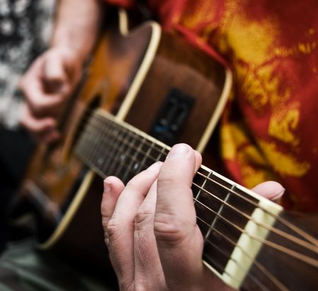 A close up of a guitarists hands playing acoustic guitar. Narrow depth of field. Stock Photo