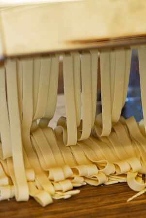 Freshly made pasta coming out of the pasta machine.