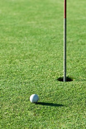 A golf ball a short putt away from the hole with the flag still in it. Stock Photo