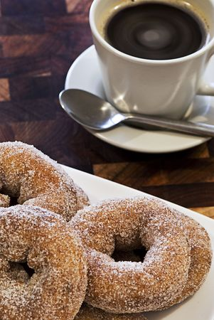A plate piled high with donuts in front of a hot cup of coffee. Stock Photo