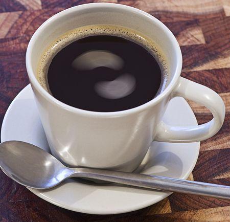 Una taza de café sentado en un platillo interesante con remolinos en líquido. Foto de archivo - 4397168