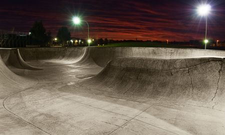 on ramp: A skate park at night with lights on and sunset sky.