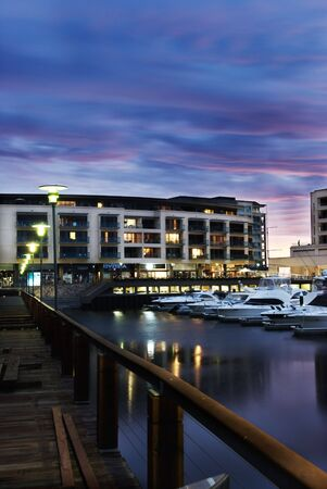 Boats in a Marina with luxury apartments in the background Stock Photo