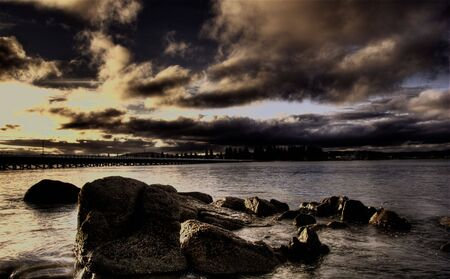 brooding: A brooding sunset over the sea with rocks in the foreground and causeway in the background. Stock Photo