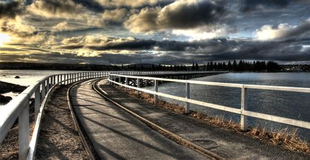A train track leading the way accross a jetty to the mainland. Taken at sunset with a brooding sky.