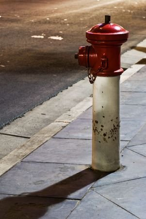 A red fire hydrant on the footpath taken at night.