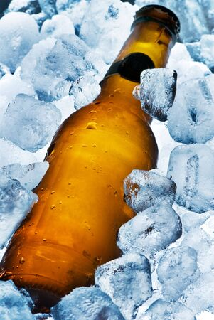 A beer bottle sitting in a container of ice. Cold and ready to drink. Stock Photo