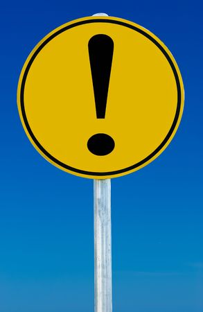 ad: A road sign with an exclamation mark on it isolated on a blue sky. Stock Photo