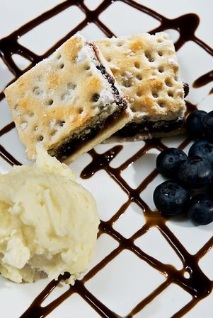 A yummy desert with ice cream, blueberries and chocolate sauce.