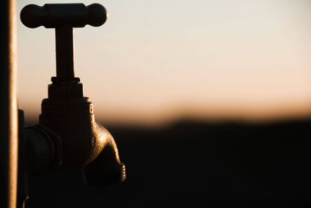 A close up view of a tap looking out over a sunset landscape.