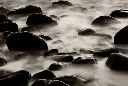 The capture of water rushing through rocks. Stock Photo