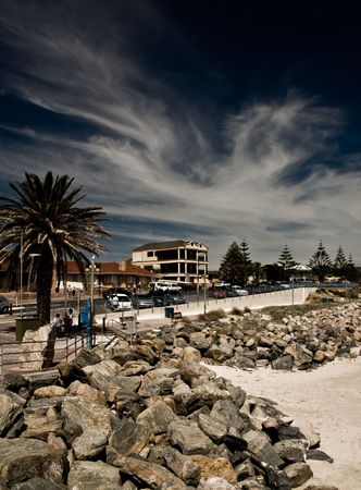 buidings: A town situated on the coast. Beach and rocks in foreground with dynamic sky. Stock Photo