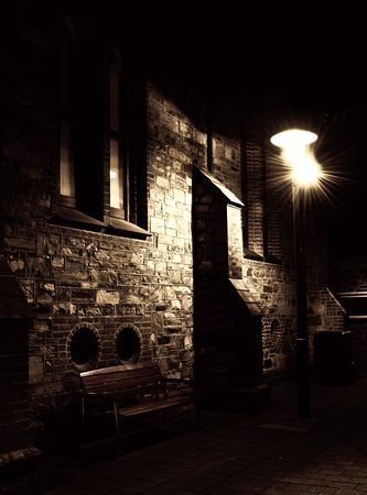 A bench in a dark alley way illuminated by a lamp post.