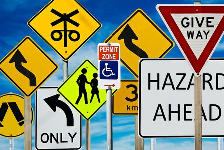 Multiple road signs against a blue cloudy sky. Signs include: giveway, hazard, pedestrian crossing, left turn only, railway crossing and more.