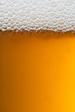 A close up of a glass of beer with lovely amber colour and white frothy bubbles on top.