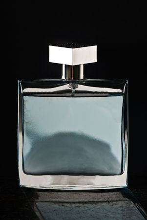 A bottle of perfume isolated on a black background with a reflection on black granite.