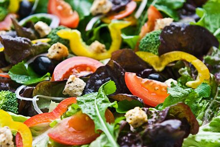 A healthy salad made up of lettuce, tomato, peppers, olives croutons and onion. Stock Photo